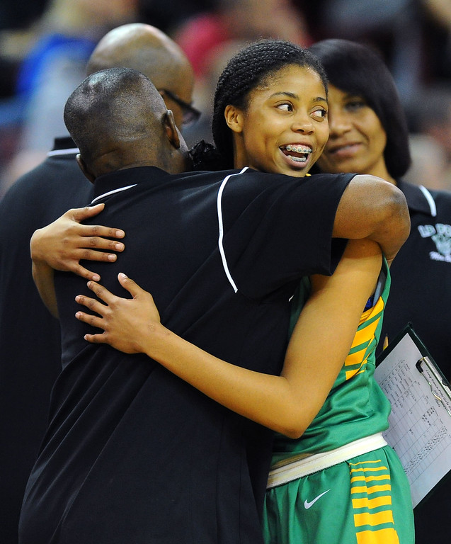 . After fouling out, Poly\'s Arica Carter gets a hug from an assistant coach at Sleep Train Arena in Sacramento, CA on Saturday, March 29, 2014. Long Beach Poly vs Salesian in the CIF Open Div girls basketball state final. 2nd half. Poly won 70-52. (Photo by Scott Varley, Daily Breeze)