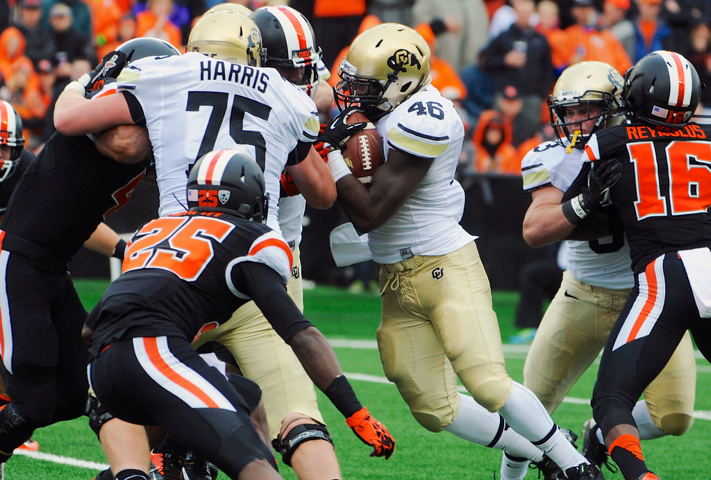 . Oregon State defends a run by Colorado\'s Christian Powell (46) during the first half of an NCAA college football game in Corvallis, Ore., Saturday, Sept 28, 2013. (AP Photo/Greg Wahl-Stephens)