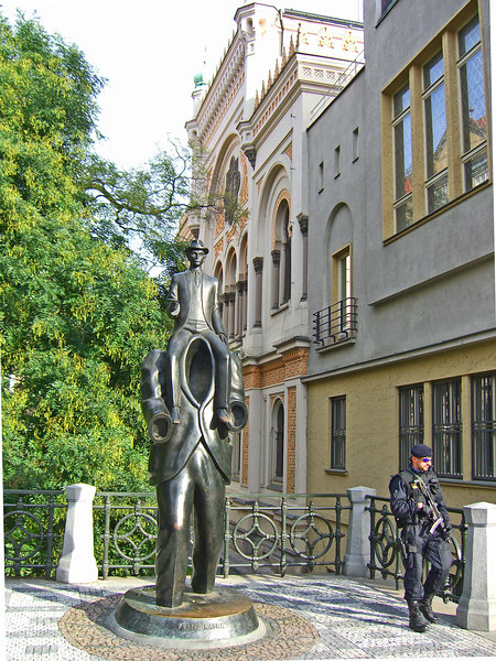 Outside the Spanish Synagogue: A statue of Franz Kafka and a Czech police officer on high security patrol for the Jewish holidays.