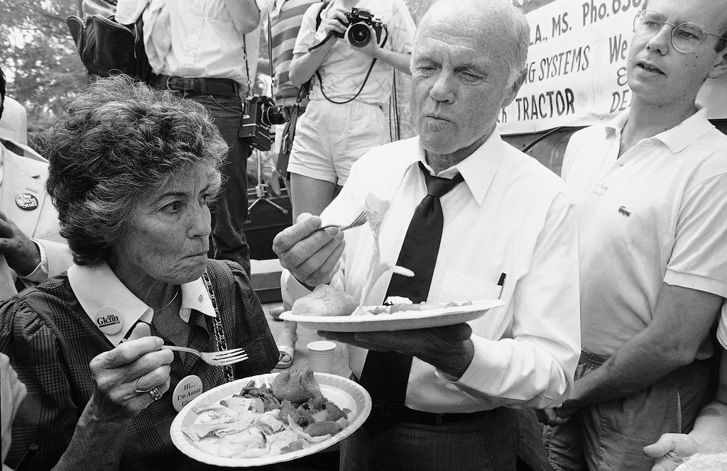 . Presidential hopeful John Glenn, center, and his wife Annie Glenn, left, enjoy some home cooked food while campaigning at the Neshoba County Fair, July 29, 1983, near Philadelphia, Miss. Glenn was a guest speaker at the fair and told a large crowd that the toughest times may still lie ahead in the nations efforts to achieve civil rights. The man on the right is unidentified. (AP Photo/Tannen Maury)