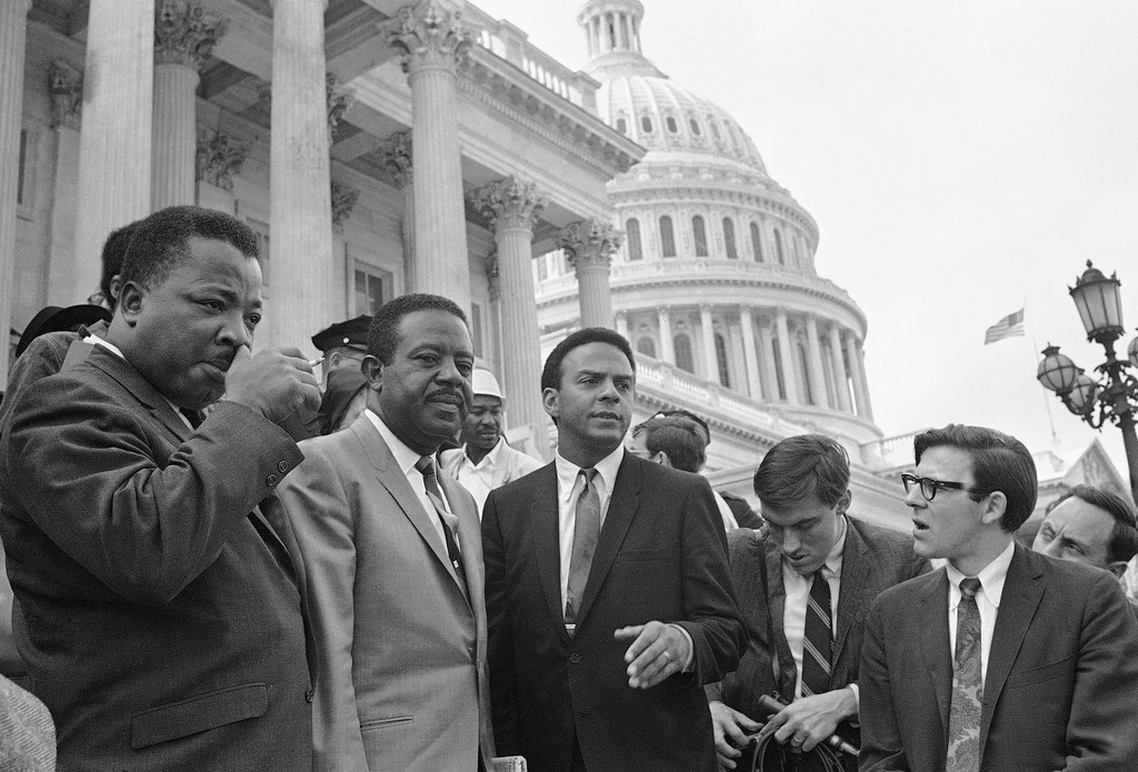 . Civil rights leader Rev. Ralph Abernathy, second from left, discusses the second day of the Poor People\'s Campaign in Washington from the steps of the Capitol, April 30, 1968. With him are A.D. King, left, brother of the late Dr. Martin Luther King, Jr., who was assassinated April 4, and Andrew Young, center.  Others are unidentified. (AP Photo)