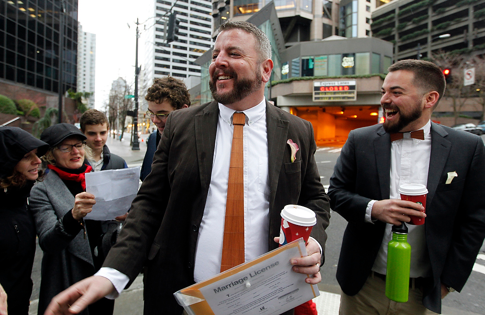 ". Keith Bacon, center, holds a marriage license as his partner Corianton Hale, right, and friends sing ""Going to the Chapel\"" as they wait at Seattle City Hall to become among the first gay couples to legally wed in the state, Sunday, Dec. 9, 2012, in Seattle. (AP Photo/Elaine Thompson)"