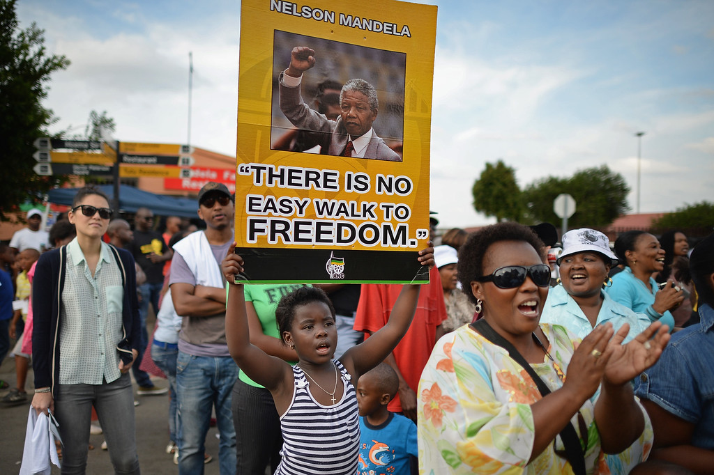 . ANC supporters sing and dance to celebrate the life of Nelson Mandela outside his former home in Vilakazi Street, Soweto Township, on December 7, 2013 in Soweto, South Africa. Mandela, also known as Madiba, passed away on the evening of December 5th, 2013 at his home in Houghton at the age of 95. (Photo by Jeff J Mitchell/Getty Images)