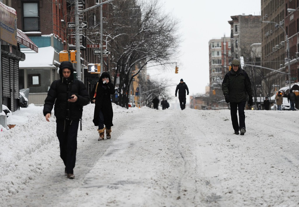 . People walk on a deserted Lexington Avenue during what is normally a crowed morning rush hour after a snowstorm hit New York January 27, 2015. AFP PHOTO/Stan  HONDA/AFP/Getty Images