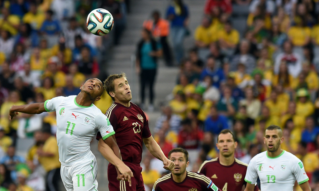 . Russia\'s defender Dmitry Kombarov (R) challenges Algeria\'s midfielder Yacine Brahimi for the ball during the Group H football match between Algeria and Russia at The Baixada Arena in Curitiba on June 26, 2014, during the 2014 FIFA World Cup. PHILIPPE DESMAZES/AFP/Getty Images