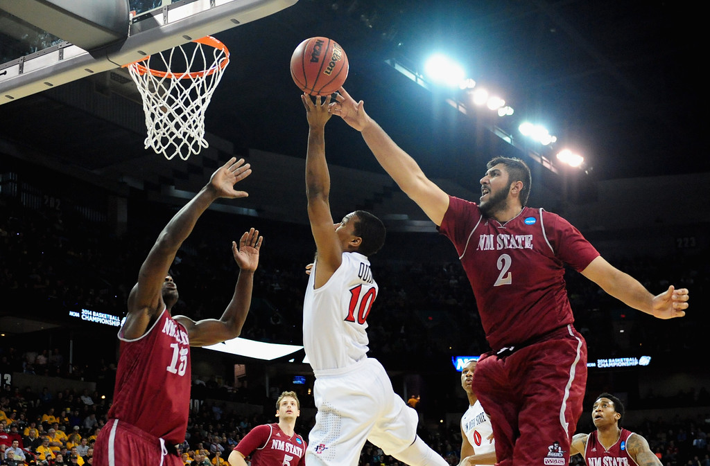 . SPOKANE, WA - MARCH 20:  Sim Bhullar #2 of the New Mexico State Aggies tries to block Aqeel Quinn #10 of the San Diego State Aztecs during the second round of the 2014 NCAA Men\'s Basketball Tournament at Spokane Veterans Memorial Arena on March 20, 2014 in Spokane, Washington.  (Photo by Steve Dykes/Getty Images)