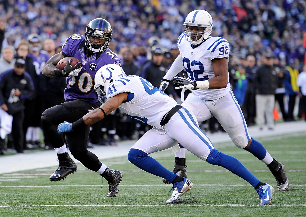 . Baltimore Ravens running back Bernard Pierce (30) tries to avoid Indianapolis Colts free safety Antoine Bethea (41) and outside linebacker Jerry Hughes (92) during the first half of an NFL wild card playoff football game Sunday, Jan. 6, 2013, in Baltimore. (AP Photo/Nick Wass)