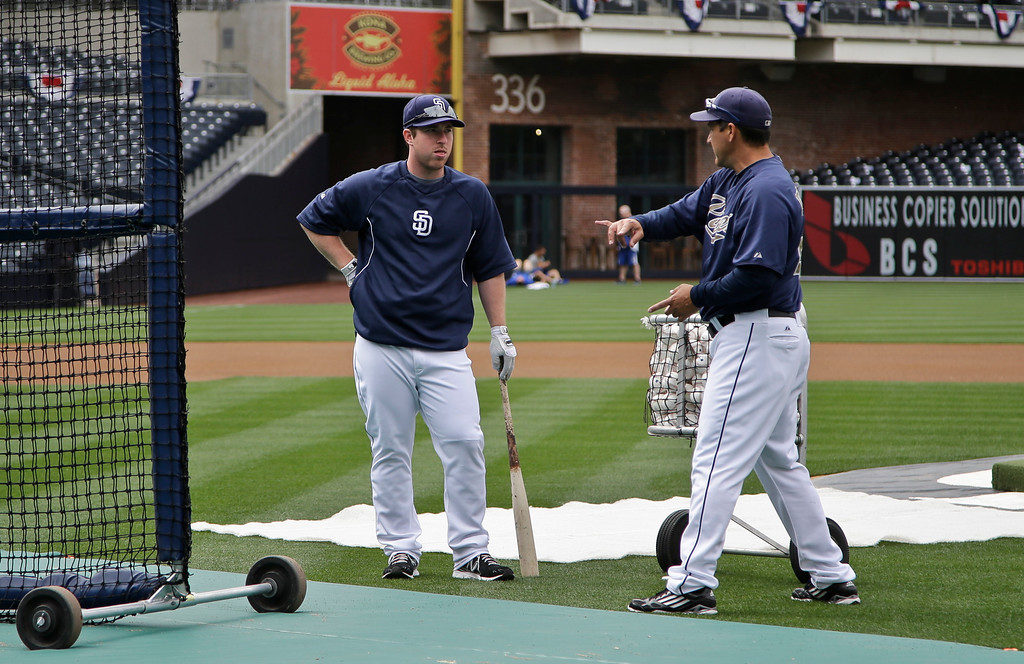 . San Diego Padres batting coach Phil Plantier, right, talks with Padres\' third baseman Jedd Gyorko during early extra hitting practice before the Padres\' baseball game against the Los Angeles Dodgers in San Diego, Thursday, April 11, 2013. (AP Photo/Lenny Ignelzi)