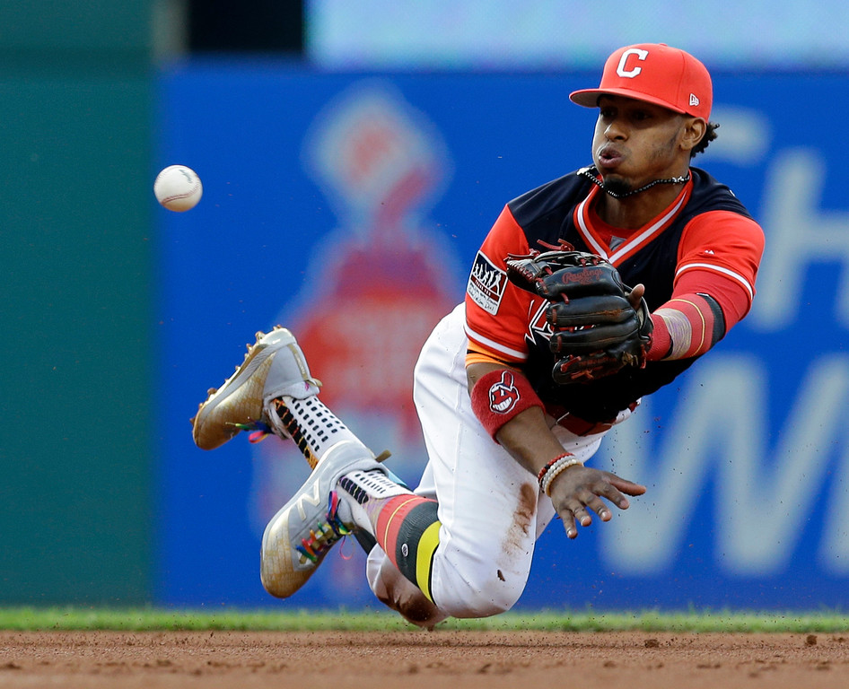 . Cleveland Indians\' Francisco Lindor tosses the ball from his mitt to second baseman Jose Ramirez to get Kansas City Royals\' Lorenzo Cain out at second base during the first inning of a baseball game, Friday, Aug. 25, 2017, in Cleveland. Melky Cabrera was out at first base for the double play. (AP Photo/Tony Dejak)