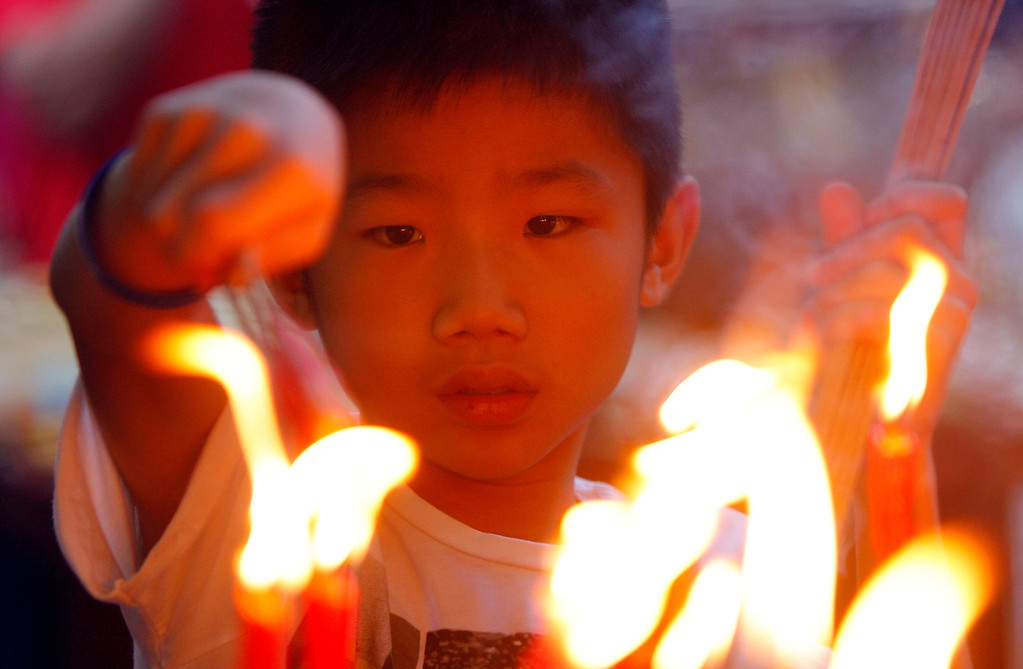 . An ethnic Chinese boy lights candles and joss sticks on the first day of the Chinese Lunar New Year at a temple in Kuala Lumpur, Malaysia, Friday, Jan. 31, 2014. Ethnic Chinese Malaysians swarmed the temple to pray for good fortune. (AP Photo/Lai Seng Sin)