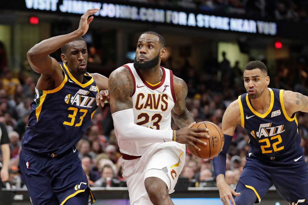 . Cleveland Cavaliers\' LeBron James, center, drives between Utah Jazz\'s Ekpe Udoh, left, and Thabo Sefolosha, from Switzerland, in the second half of an NBA basketball game, Saturday, Dec. 16, 2017, in Cleveland. (AP Photo/Tony Dejak)