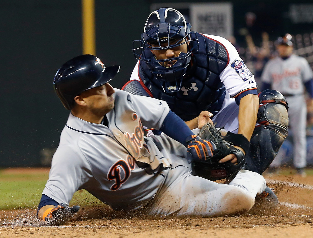 . Detroit Tigers� Jose Iglesias, left, is tagged out by Minnesota Twins catcher Kurt Suzuki as he tried to score from third on a flyout by Victor Martinez in the seventh inning of a baseball game, Monday, April 27, 2015, in Minneapolis. The Tigers won 5-4. (AP Photo/Jim Mone)
