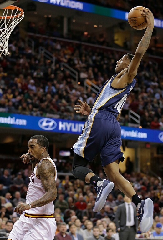 . Memphis Grizzlies\' Troy Williams, right, dunks the ball over Cleveland Cavaliers\' J.R. Smith in the second half of an NBA basketball game, Tuesday, Dec. 13, 2016, in Cleveland. The Cavaliers won 103-86. (AP Photo/Tony Dejak)
