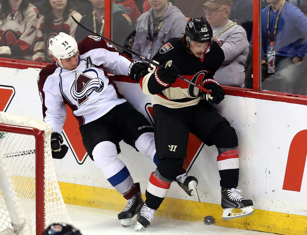 . Ottawa Senators Erik Karlsson (65) battles for the puck with Colorado Avalanche\'s Cody McLeod (55) during first-period NHL hockey game action in Ottawa, Ontario, Sunday March 16, 2014. (AP Photo/The Canadian Press, Fred Chartrand)