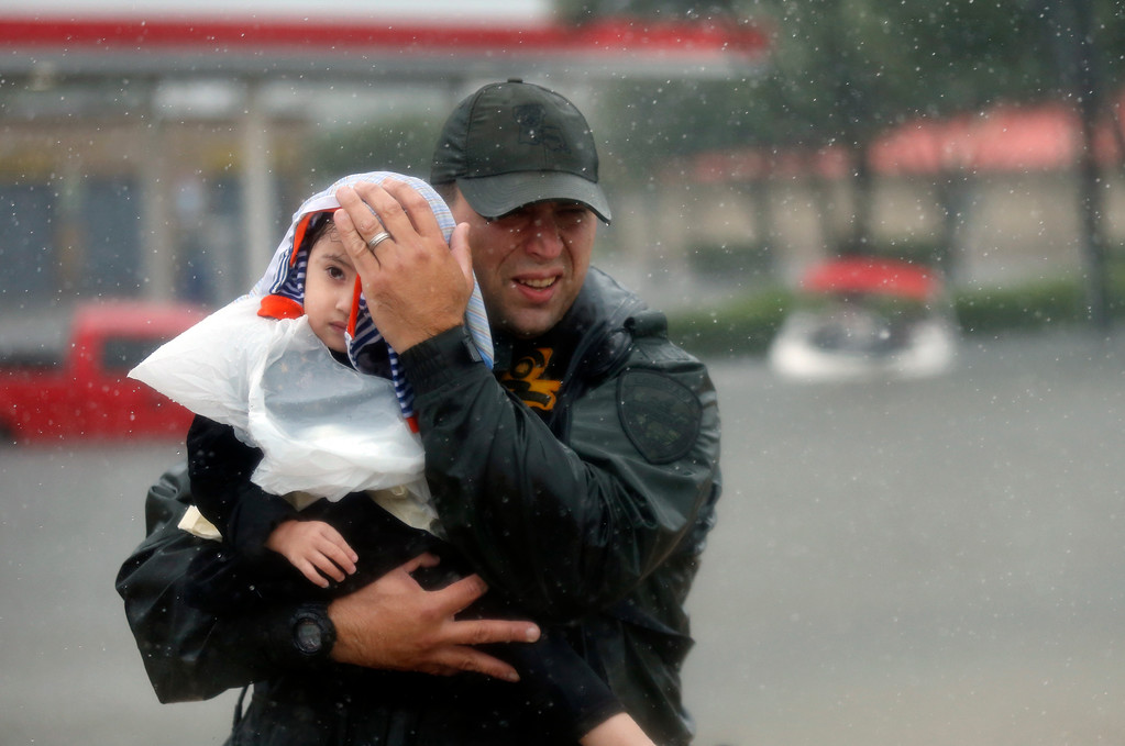 . Sgt. Chad Watts, of the Louisiana Department of Wildlife and Fisheries, holds Madelyn Nguyen, 2, after he rescued her and her family by boat from floodwaters of Tropical Storm Harvey, which hit Texas last week as a Category 4 hurricane, in Houston, Monday, Aug. 28, 2017. (AP Photo/Gerald Herbert)