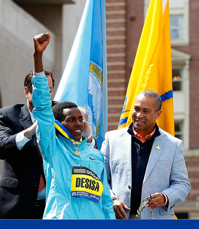 . Lelisa Desisa Benti (L) of Ethiopia reacts after winning the men�s division of the 117th Boston Marathon as Duval Patrick, governor of Massachusetts watches on April 15, 2013 in Boston, Massachusetts.  (Photo by Jim Rogash/Getty Images)