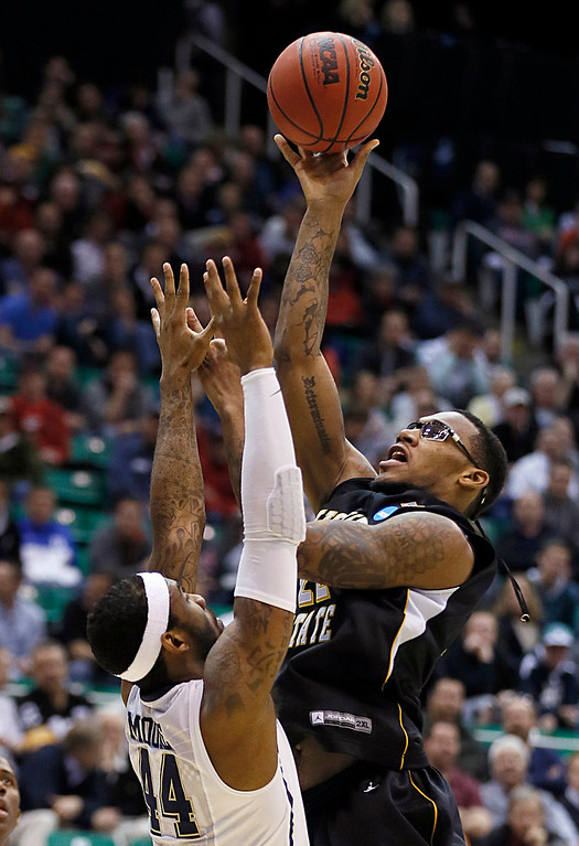 . Wichita State\'s Carl Hall, right, shoots over Pittsburgh\'s J.J. Moore in the second half during a second-round game in the NCAA college basketball tournament in Salt Lake City Thursday, March 21, 2013. (AP Photo/George Frey)