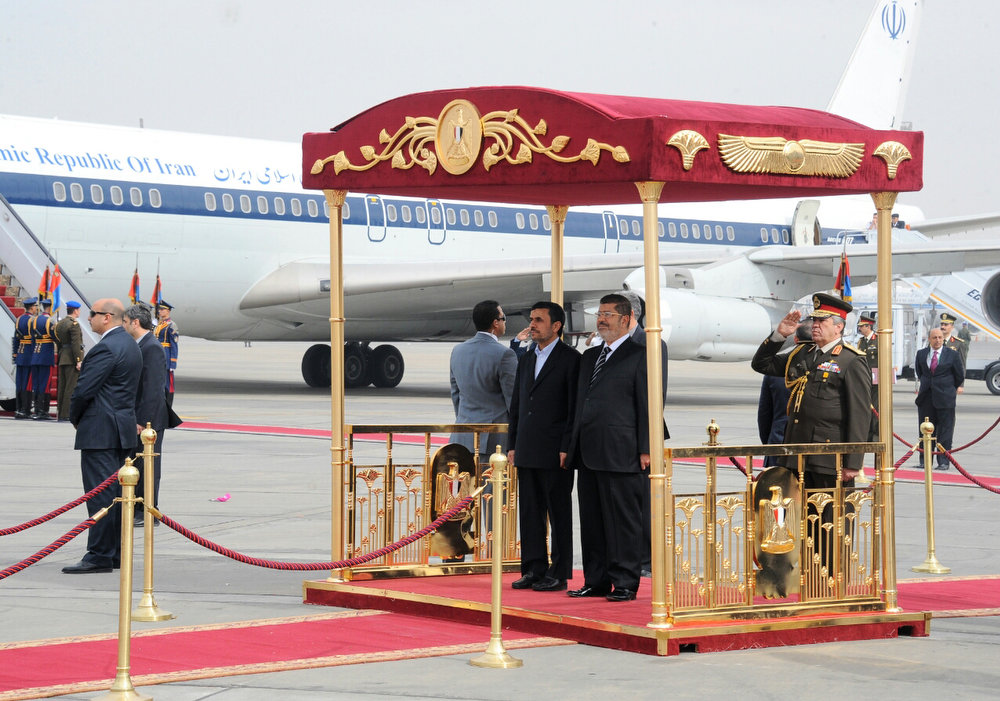 Description of . In this image released by the Egyptian Presidency, Iran's President Mahmoud Ahmadinejad, center, and Egyptian President Mohammed Morsi, center right, participate in an arrival ceremony at the airport in Cairo, Egypt, Tuesday, Feb. 5, 2013. Ahmadinejad arrived in Cairo on Tuesday for the first visit by an Iranian leader in more than three decades, marking a historic departure from years of frigid ties between the two regional heavyweights.(AP Photo/Egyptian Presidency)