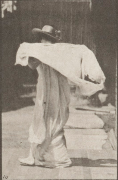 Semi-nude woman lifting shawl, putting it around shoulders and turning
