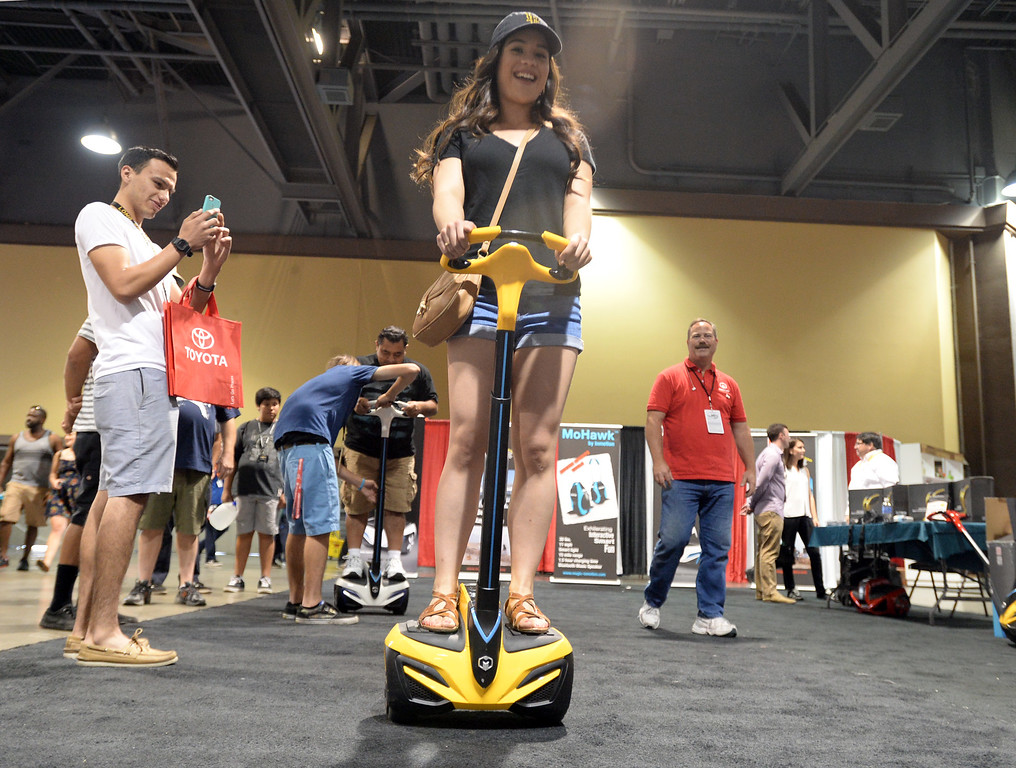 . People give InMotion, a stand-up motorized scooter, a trial run in the Lifestyle Expo of theToyota Grand Prix of Long Beach Friday, April 17, 2015, Long Beach, CA.   Photo by Steve McCrank/Staff Photographer