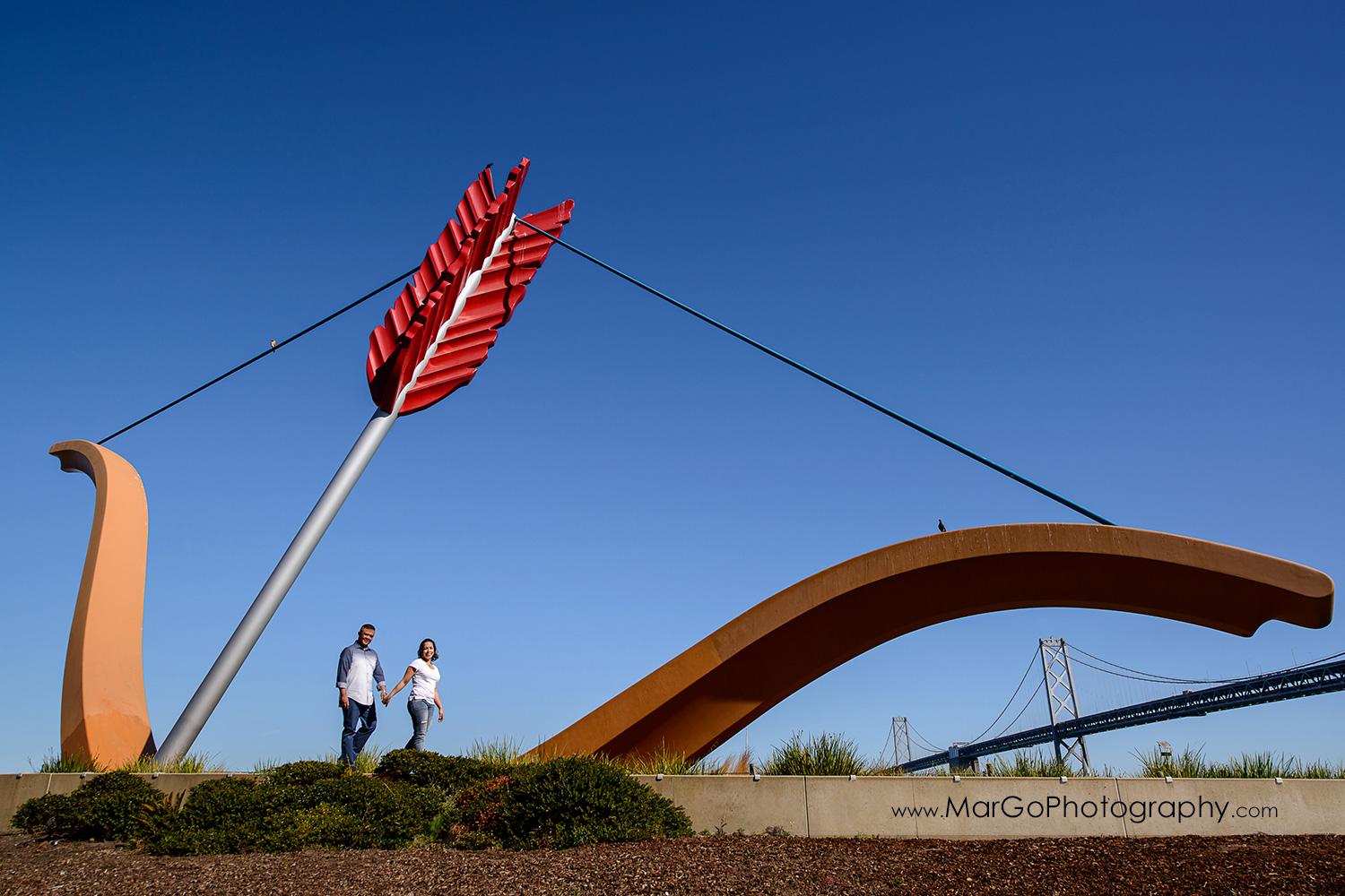 engagement session at Rincon Park in San Francisco - couple walking in front of Cupid's Span with Bay Bridge under the bow