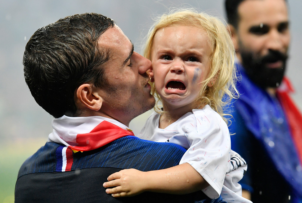 . France\'s Antoine Griezmann carries his crying daughter after his team won the final match between France and Croatia at the 2018 soccer World Cup in the Luzhniki Stadium in Moscow, Russia, Sunday, July 15, 2018. (AP Photo/Martin Meissner)