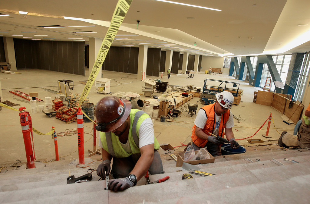 . Herman Negron, left, and Chris Allen work on the stairs leading down to the meeting room area in the new 125,000-square-foot expansion of the San Jose McEnery Convention Center in San Jose, Calif. on Tuesday, Aug. 6, 2013.  (Gary Reyes/Bay Area News Group)