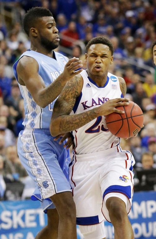 . Kansas guard Ben McLemore (23) drives on North Carolina guard/forward Reggie Bullock (35) during the first half of a third-round game in the NCAA college basketball tournament at the Sprint Center in Kansas City, Mo., Sunday, March 24, 2013. (AP Photo/Orlin Wagner)