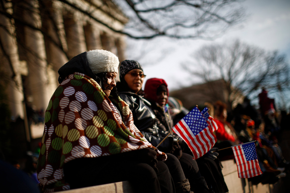 Description of . People sit on a wall at the National Mall for the ceremonial swearing-in on the West front of the U.S. Capitol in Washington January 21, 2013. REUTERS/Eric Thayer