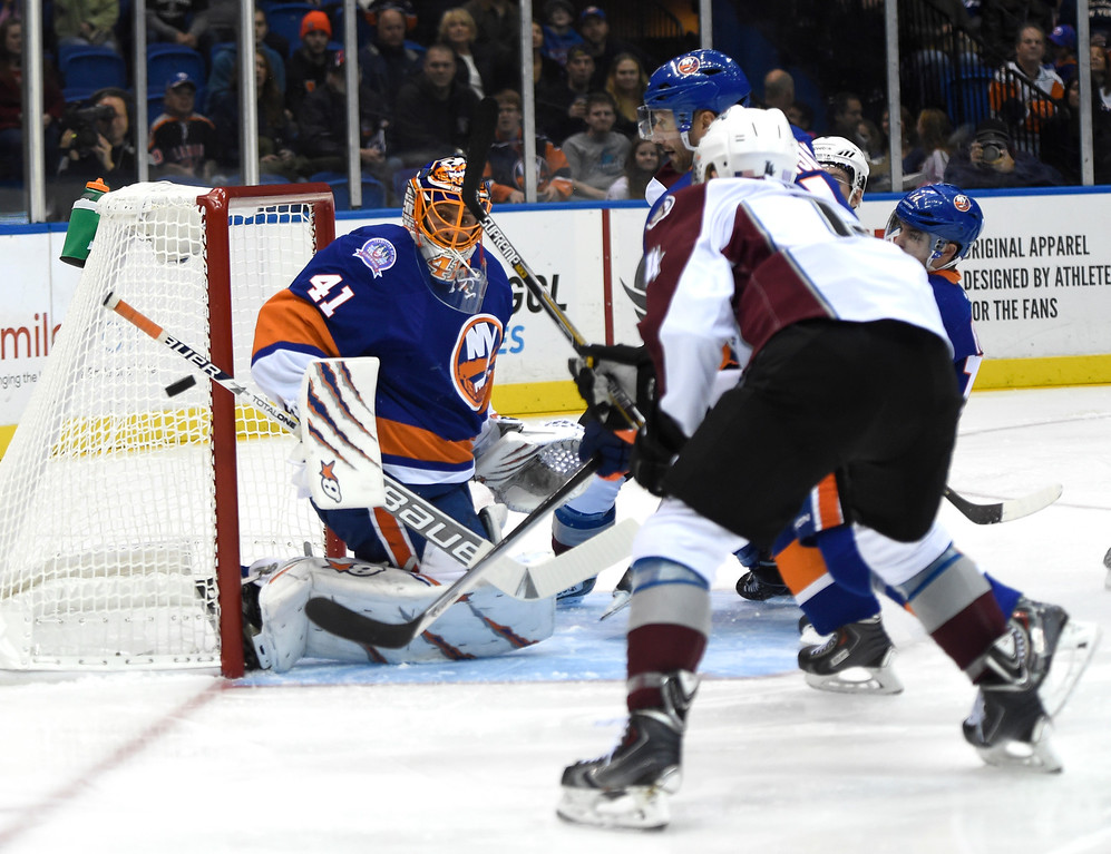 . New York Islanders goalie Jaroslav Halak (41) blocks a shot on goal as Colorado Avalanche defenseman Tyson Barrie (4) looks on in the first period of an NHL hockey game at Nassau Coliseum on Tuesday, Nov. 11, 2014, in Uniondale, N.Y. (AP Photo/Kathy Kmonicek)