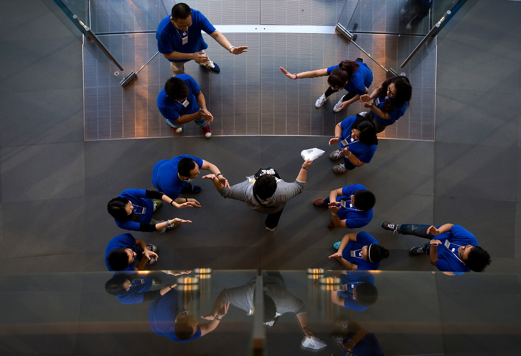 . Chinese employees cheer a customer after he bought new iPhone at an Apple store in Wangfujing shopping district in Beijing on Friday, Sept. 20, 2013. Apple released the iPhone 5S and 5C models on Friday. (AP Photo/Andy Wong)