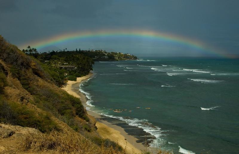 Rainbow from Diamond Head Bluff   Surfers paddling out to surf  O'ahu, Hawai'i