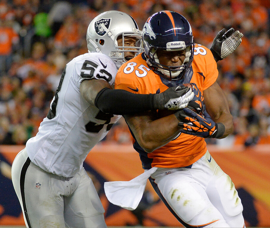 . Denver Broncos tight end Virgil Green (85) is tackled by Oakland Raiders middle linebacker Nick Roach (53) in the third quarter in Denver. (Photo by John Leyba/The Denver Post)