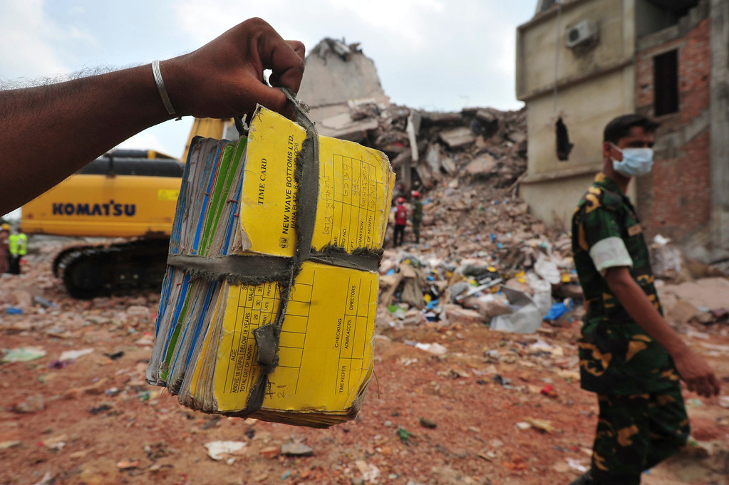 . A rescue worker holds a a stack of files of a garment factory that was found from the rubble of the collapsed Rana Plaza building in Savar, around 30 km (19 miles) outside Dhaka April 30, 2013.  REUTERS/Khurshed Rinku