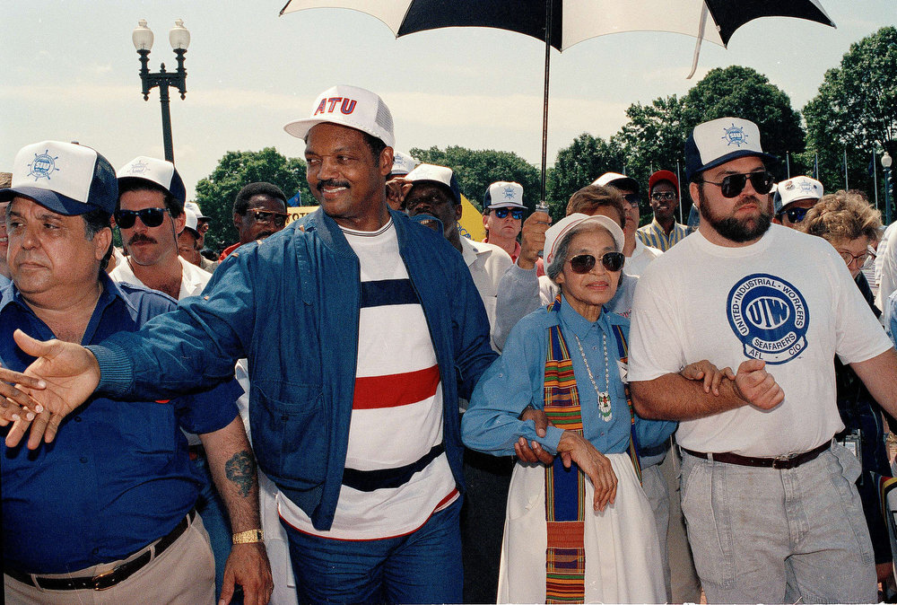 Description of . The Rev. Jesse Jackson, left center, and civil rights movement pioneer Rosa Parks, right center, join striking Greyhound workers at a rally in front of Union Station in Washington, June 19, 1990.  Jackson urged the bus riding public to boycott the company.  (AP Photo/J. Scott Applewhite)
