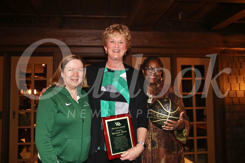 Head of School Elizabeth McGregor, coach Melanie Horn with her plaque of appreciation, and alumna mom Akila Gibbs with a basketball signed by the team