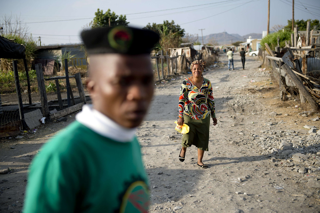 . A woman and a union representative walk the dirt path in the Nkaneng shantytown next to the platinum mine, run by British company Lonmin, in Marikana. On August 16, 2012, police at the Marikana mine open fire on striking workers, killing 34 and injuring 78, during a strike was for better wages and living conditions. Miners still live in dire conditions despite a small wage increase.  ODD ANDERSEN/AFP/Getty Images