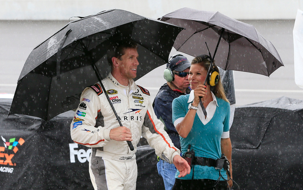 . Carl Edwards talks with Jaime Little, pit reporter for NASCAR coverage on Fox during a rain delay at the NASCAR Sprint Cup series auto race at Michigan International Speedway, Sunday, June 14, 2015, in Brooklyn, Mich. (AP Photo/Carlos Osorio)