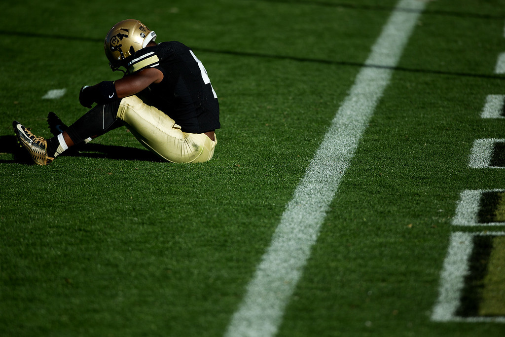 . BOULDER, CO - OCTOBER 25:  Defensive back Chidobe Awuzie #4 of the Colorado Buffaloes sits near the end zone in disappointment after the Buffs were defeated by the UCLA Bruins 40-37 in double overtime at Folsom Field on October 25, 2014 in Boulder, Colorado. (Photo by Justin Edmonds/Getty Images)