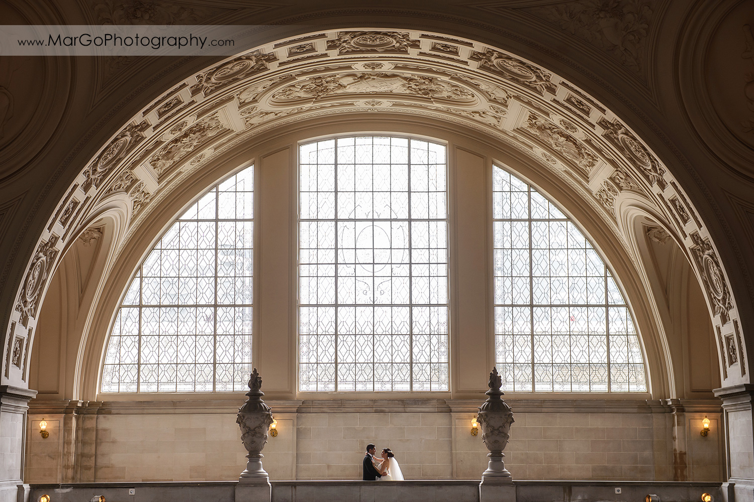bride and groom with the big window in San Francisco City Hall
