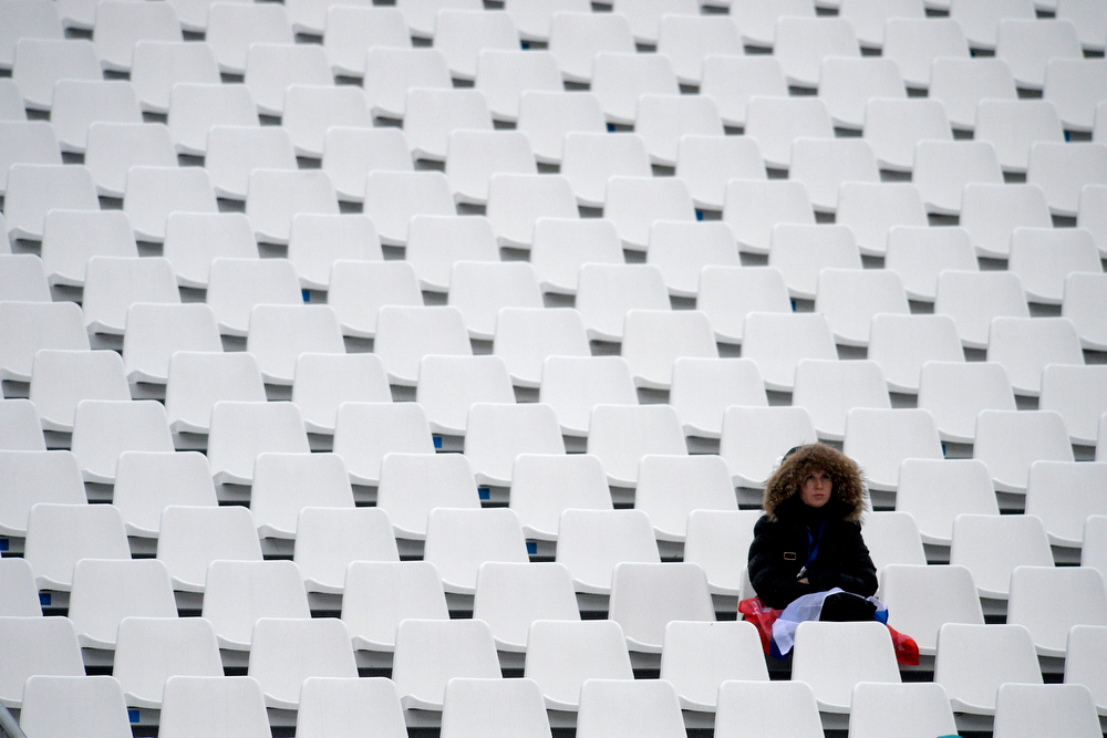Description of . A fan sits in dampened conditions during the first round of the ladies' giant slalom. Sochi 2014 Winter Olympics on Tuesday, February 18, 2014. (Photo by AAron Ontiveroz/The Denver Post)