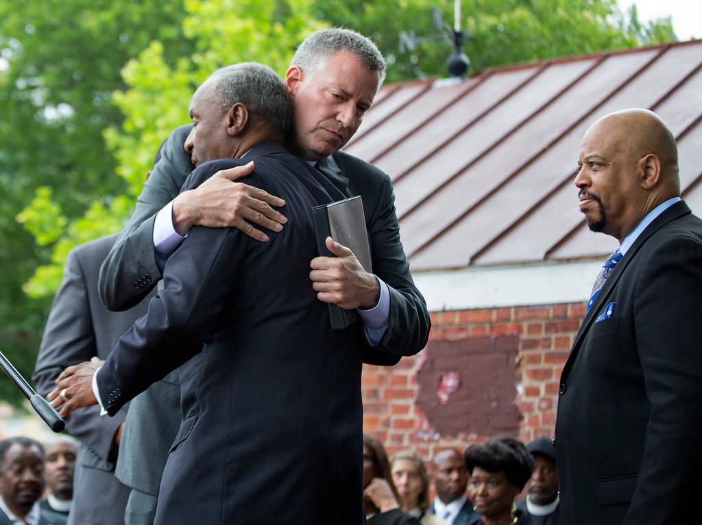 . New York City Mayor Bill de Blasio, center, embraces Rev. Floyd Flake of the Greater Allen A.M.E. Cathedral before addressing people at a rally in the Queens borough of New York Saturday, June 20, 2014, in the wake of the shootings at Emanuel A.M.E. Church in Charleston, S.C. earlier in the week. (AP Photo/Craig Ruttle)