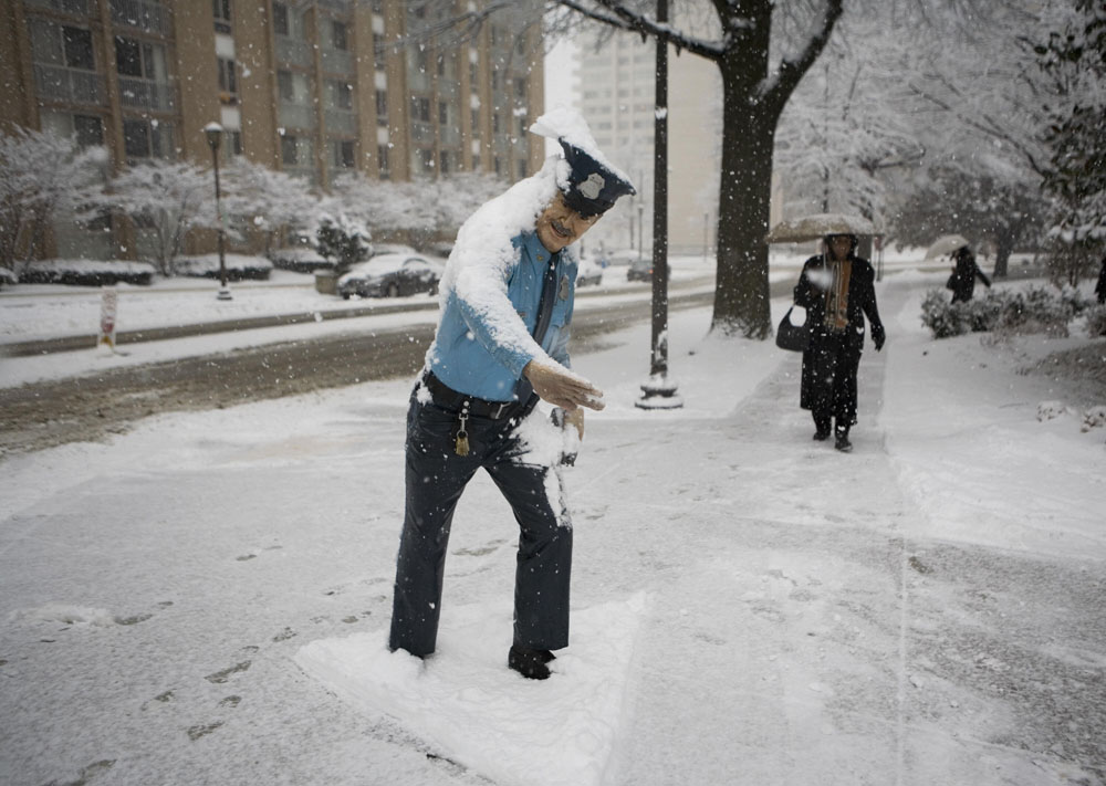 Description of . A woman walks next to a snow-covered statue of a policeman directing traffic 25 February 2007 in Chevy Chase, Maryland. A winter storm warning is in effect until early 26 February, with moderate to heavy snow fall expected through the afternoon. AFP PHOTO/Mandel NGAN