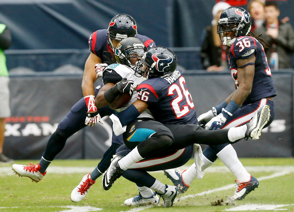 . Houston Texans defensive back Brandon Harris (26) tackles Jacksonville Jaguars wide receiver Ace Sanders (18) during the first quarter an NFL football game Sunday, Nov. 24, 2013, in Houston. (AP Photo/Patric Schneider)