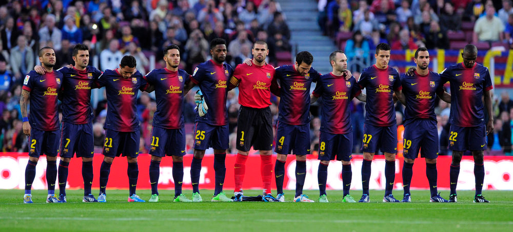 Description of . (L-R) Barcelona's Brazilian defender Dani Alves, Barcelona's forward David Villa, Barcelona's Brazilian defender Adriano, Barcelona's midfielder Thiago Alcantara, Barcelona's Cameroonian midfielder Alex Song, Barcelona's goalkeeper Victor Valdes, Barcelona's midfielder Cesc Fabregas, Barcelona's midfielder Andres Iniesta, Barcelona's forward Cristian Tello, Barcelona's defender Martin Montoya and Barcelona's French defender Eric Abidal hold a minute's silence in memory of those killed in the Boston Marathon bombings before the Spanish league football match FC Barcelona vs Levante UD at the Camp Nou stadium in Barcelona on April 20, 2013.   JOSEP LAGO/AFP/Getty Images