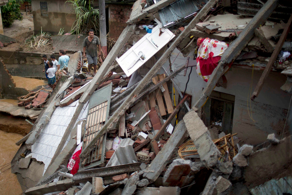 Description of . Residents stand near a home damaged by a flood caused by heavy rains in the Xerem neighborhood, about 31 miles north of Rio de Janeiro, Brazil, Thursday, Jan. 3, 2013. Nearly 8.5 inches of rain fell in just 24 hours in the mountainous region north of Rio. Hard rains in Brazil are creating a state of alert in Rio de Janeiro and in nearby spots where flood-triggered mudslides have killed hundreds in recent years.  (AP Photo/Felipe Dana)