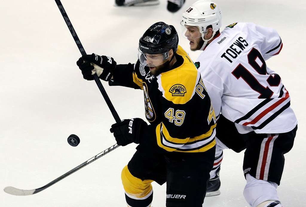 . Boston Bruins center Rich Peverley (49) and Chicago Blackhawks center Jonathan Toews (19) fight for the loose puck during the first period in Game 3 of the NHL hockey Stanley Cup Finals in Boston, Monday, June 17, 2013. (AP Photo/Charles Krupa)