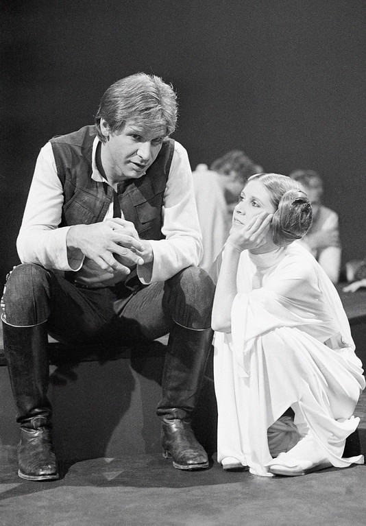 . Harrison Ford, as Han Solo of �Star Wars� fame chats with Carrie Fisher Nov. 13, 1978 during a break in the filming of the CBS-TV special �The Star Wars Holiday.� Ford says he leaves the singing in the special to Carrie, who is the daughter of Eddie Fisher and Debbie Reynolds. The film will also feature many special effects not seen on the original movie. (AP Photo/George Brich )