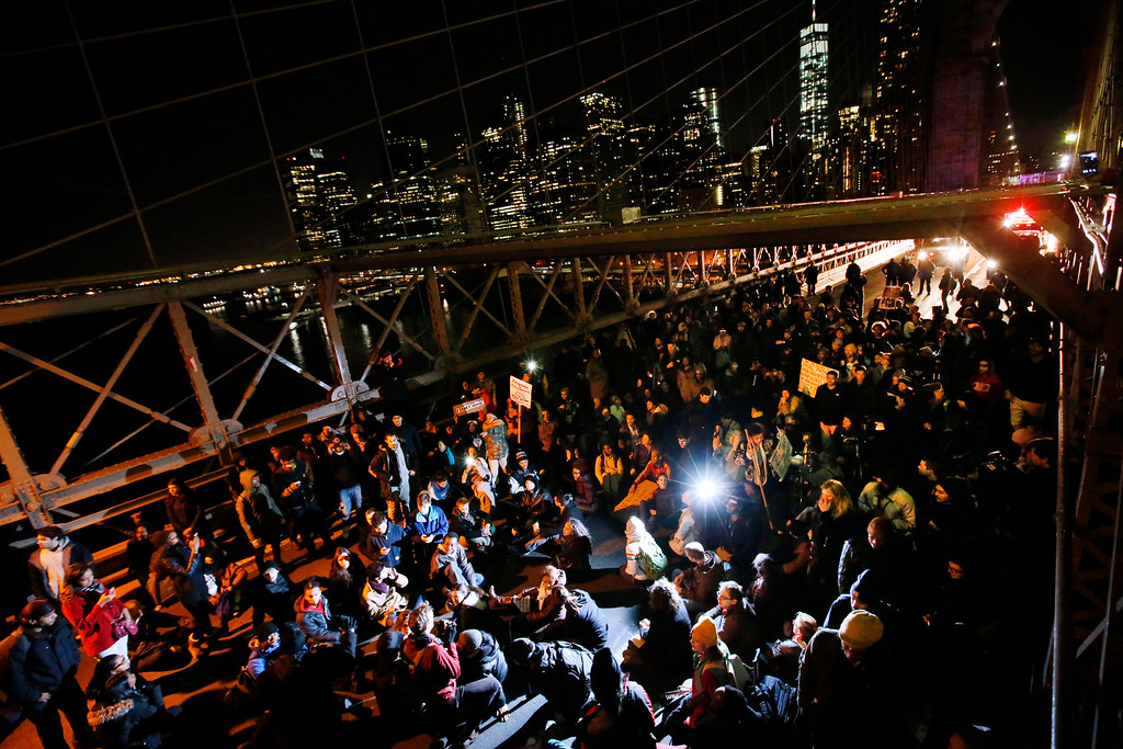 . A group of protesters rallying against a grand jury\'s decision not to indict the police officer involved in the death of Eric Garner occupies the eastbound traffic lanes of the Brooklyn Bridge in the early morning hours of Thursday, Dec. 4, 2014, in New York. (AP Photo/Jason DeCrow)