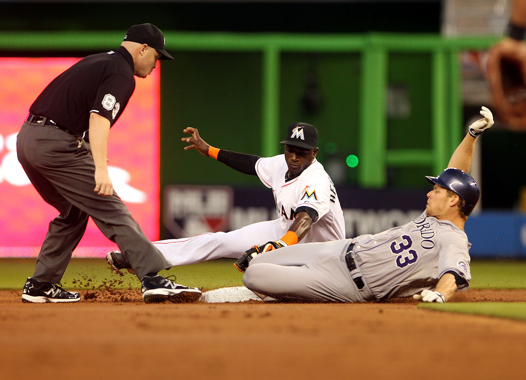 . Justin Morneau #33 of the Colorado Rockies is tagged out at second base by shortstop Adeiny Hechavarria #3 of the Miami Marlins during the second inning at the Marlins Park on April 1, 2014 in Miami, Florida.  (Photo by Marc Serota/Getty Images)